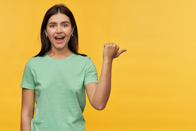Überraschte schöne junge frau mit dunklem haar in mintfarbenem t-shirt, die mit daumen isoliert über gelber wand zur seite am exemplar steht und zeigt