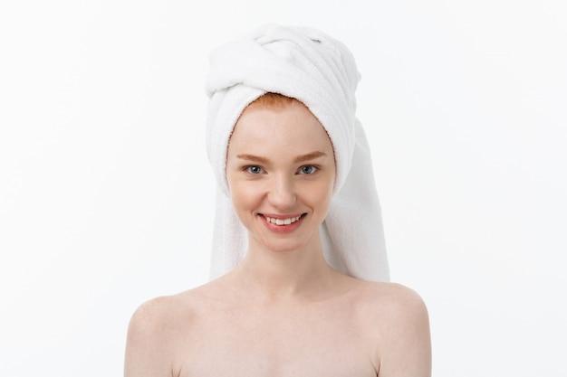 Überraschte schöne junge frau nach bad mit einem tuch auf ihrem kopf lokalisiert auf weißem hintergrund. hautpflege und spa-thema.