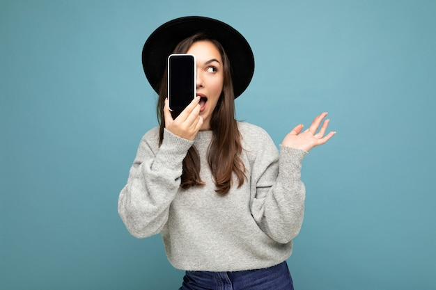 Überraschte schöne positive frau mit schwarzem hut und grauem pullover mit mobiltelefon