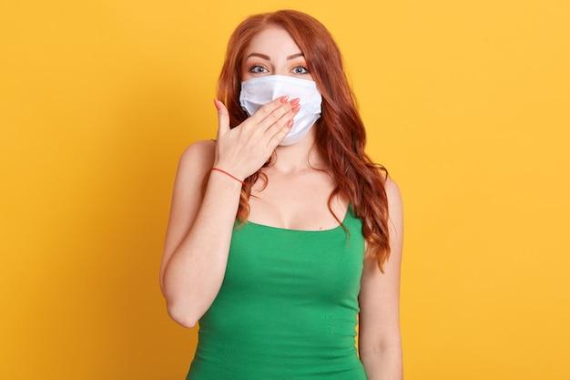 Überraschte schöne weibliche rothaarige frau, die medizinische maske trägt, die im stuporschock ist, hat erstaunten ausdruck, bedeckt ihren mund mit mund, der isoliert über gelbem hintergrund steht.