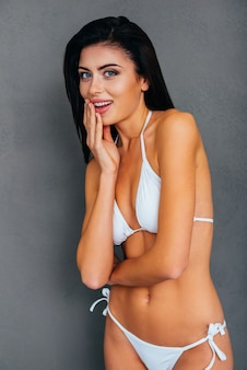 Überraschte schönheit. überraschte junge frau im weißen bikini, die ihren mund mit der hand bedeckt und die kamera anschaut, während sie vor grauem hintergrund steht