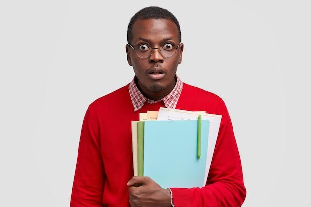 Überraschte schwarze männerstarren mit verwanzten augen, enthält die notwendige literatur, schockiert über das ergebnis der untersuchung, hat den atem angehalten