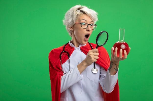 Überraschte slawische superheldenfrau in arztuniform mit rotem umhang und stethoskop in optischen gläsern betrachtet rote chemische flüssigkeit im glaskolben durch lupe auf grüner wand