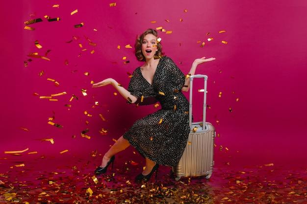 Überraschte süße frau, die mit den händen hoch posiert, kehrt von der langen reise zurück. erstaunt wunderbare dame, die auf koffer sitzt und konfetti betrachtet.