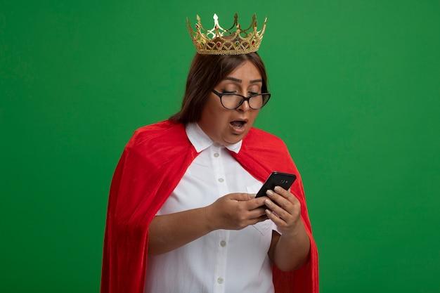 Überraschte superheldenfrau mittleren alters, die krone mit brille hält, die telefon hält und auf grün lokalisiert betrachtet