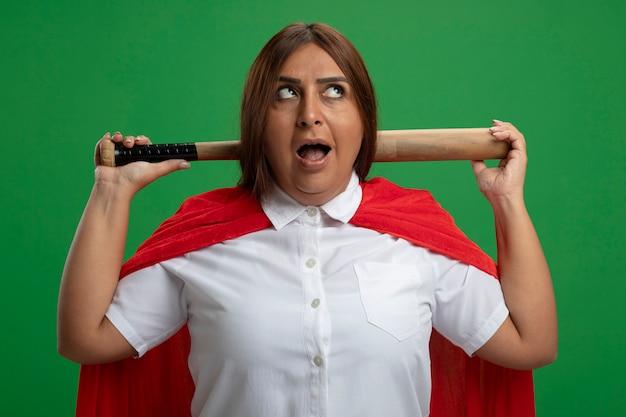 Überraschte superheldenfrau mittleren alters, die seite betrachtet baseballschläger hinter hals lokalisiert auf grün