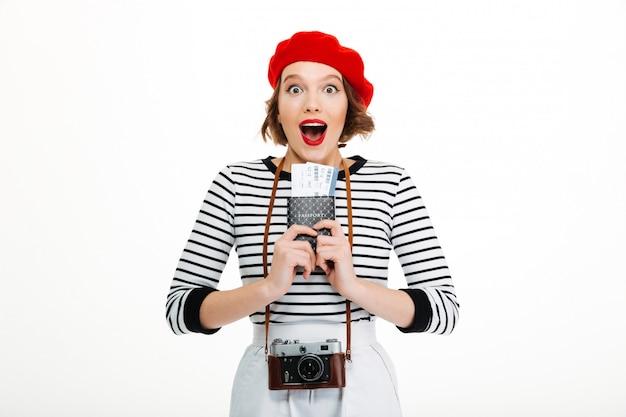 Überraschte touristische dame mit der kamera, die pass mit karten hält.