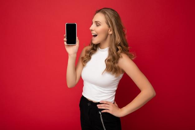 Überraschte überraschte schöne junge blonde frau, die weißes t-shirt auf rotem hintergrund mit trägt