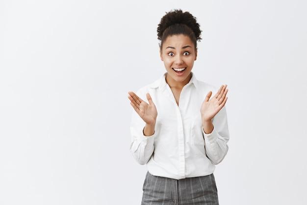 Überraschte und aufgeregte afroamerikanische unternehmerin, die erstaunt aussieht und eine großartige geschäftsmöglichkeit bietet