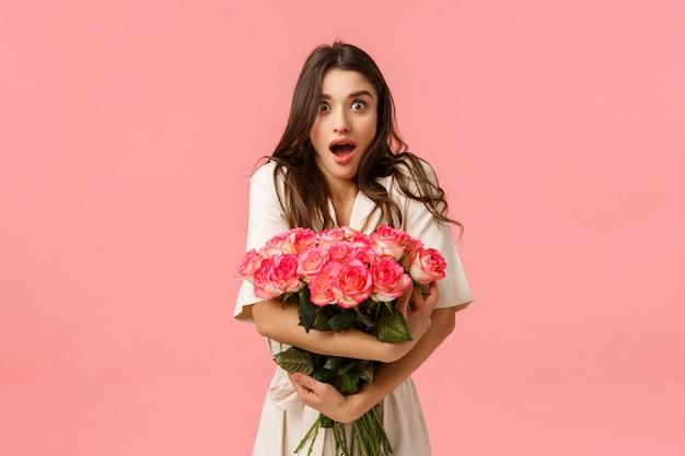 Überraschte und aufgeregte attraktive brünette freundin überrascht von unerwartetem und erstaunlichem geschenk, schickte heimlicher bewunderer schönen blumenstrauß, keuchte und sah beeindruckt aus, rosa wand