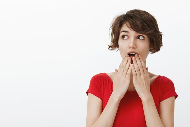 Überraschte und aufgeregte hübsche frau, die erstaunt nach luft schnappt, hört große neuigkeiten