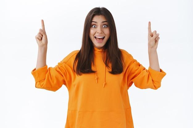 Überraschte und aufgeregte hübsche frau im orangefarbenen hoodie reagiert auf coole, unglaubliche neuigkeiten und zeigt mit dem finger nach oben, um sie über sonderpreise und tolle produkte auf lager zu informieren, weiße wand