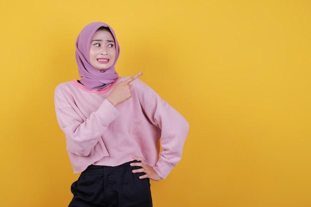 Überraschte und erschreckende schöne frau, die etwas zeigt, das weiches rosa t-shirt trägt