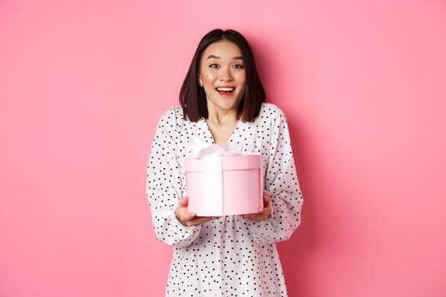 Überraschte und glückliche asiatische frau, die eine süße schachtel mit einem geschenk erhält, das über rosafarbenem hintergrund erstaunt steht