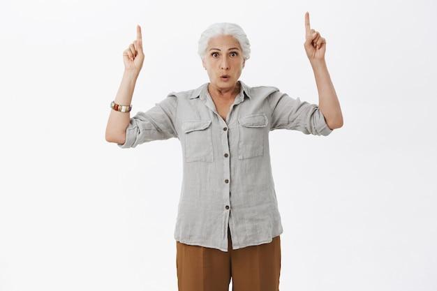 Überraschte und verblüffte oma zeigt mit den fingern nach oben und stellt fragen zum produkt nach oben