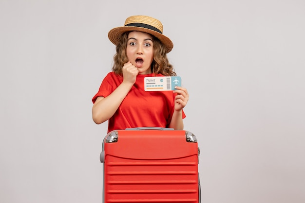 Überraschte urlaubsfrau mit rotem koffer mit ticket
