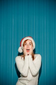 Überraschte weihnachtsfrau, die eine weihnachtsmütze trägt