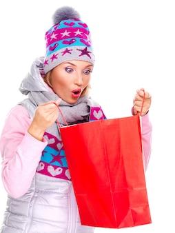 Überraschte weiße junge frau, die die geschenke in den taschen nach dem einkaufen betrachtet