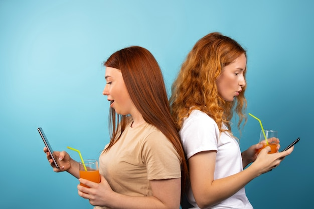 Überraschte wow-emotionen für zwei rothaarige frauen, die online auf smartphones navigieren, die rücken an rücken posieren