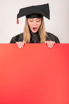 Überraschter absolvent, der ein rotes plakatmodell hält