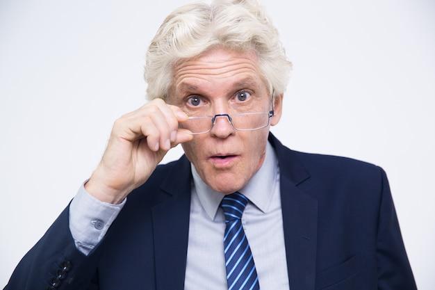 Überraschter älterer geschäftsmann über brille suchen