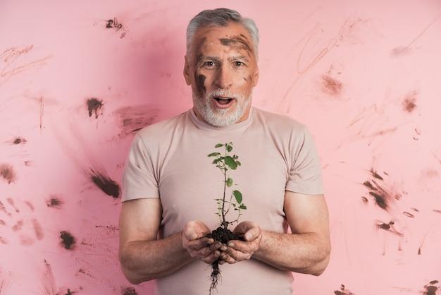 Überraschter älterer mann, der eine pflanze für das pflanzen auf einer schmutzigen wand hält