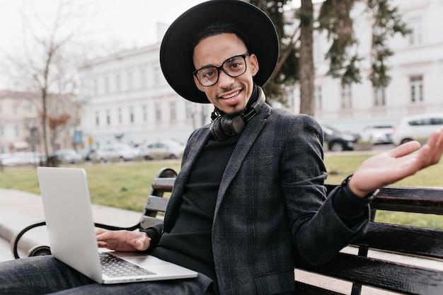 Überraschter afrikanischer student, der auf bank mit computer sitzt. foto im freien des lustigen schwarzen männlichen freiberuflers, der laptop für arbeit verwendet.