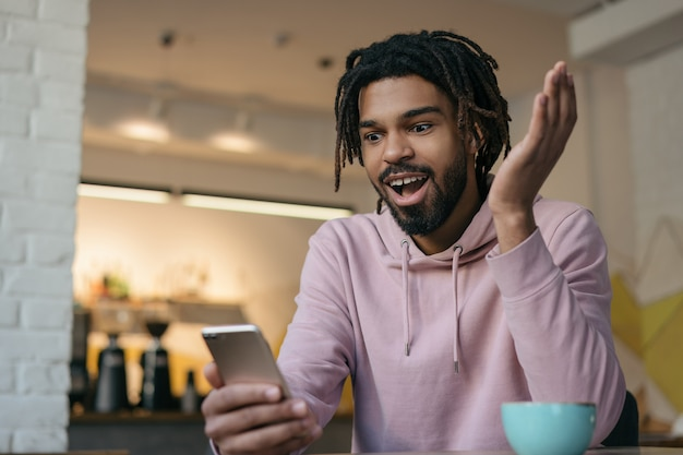 Überraschter afroamerikanermann, der smartphone hält, online einkauft, essen bestellt. porträt des lustigen emotionalen hipsters, der videos ansieht