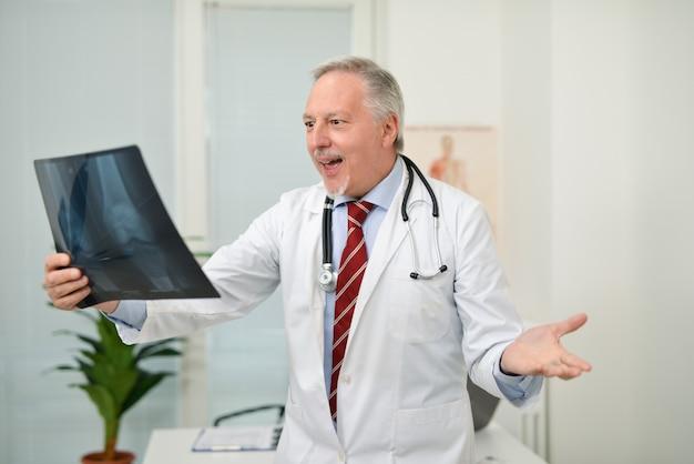 Überraschter arzt beim betrachten einer röntgenaufnahme