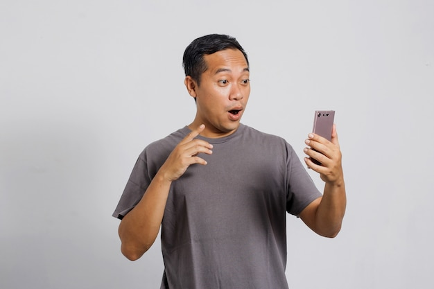 Überraschter asiatischer mann, der auf smartphone schaut