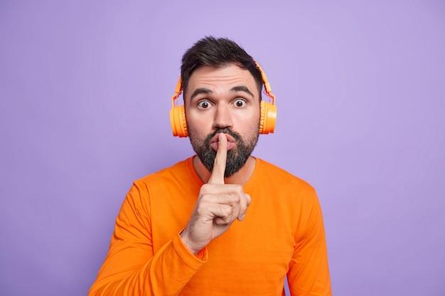 Überraschter bärtiger mann bittet darum, ruhig zu bleiben drückt zeigefinger auf die lippen sagt geheimnis trägt kopfhörer hört lieblingsmusik in orangefarbenem pullover gekleidet