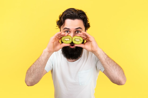 Überraschter bärtiger mann, der scheiben grüner kiwis in form einer brille vor die augen hält