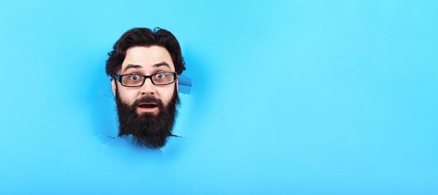 Überraschter bärtiger mann im loch im blauen hintergrund, panoramamodell
