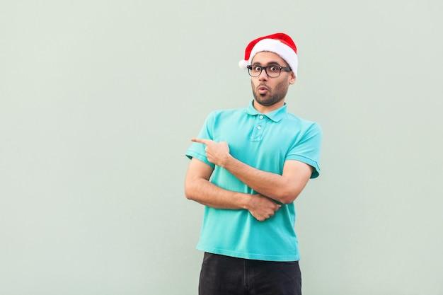 Überraschter bärtiger mann in der weihnachtstasse mit dem bart in erschüttert. wegweisend im stehen auf grauem hintergrund isoliert. blick in die kamera mit großen augen und offenem mund. studioaufnahme