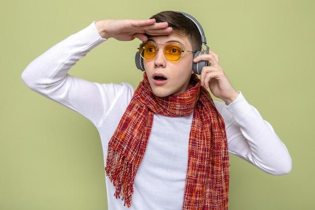 Überraschter blick in die ferne mit der hand junger gutaussehender kerl mit schal mit brille und kopfhörern