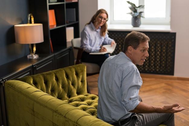 Überraschter braunhaariger mann mittleren alters, der auf der couch im büro des psychotherapeuten sitzt