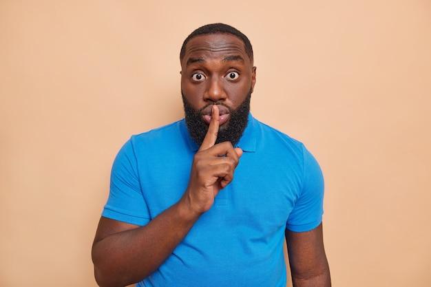 Überraschter dunkelhäutiger mann mit dickem bart drückt zeigefinger auf die lippen, macht stille geste bittet ruhig zu sein und keine gerüchte zu verbreiten trägt lässiges blaues t-shirt isoliert über beige wand