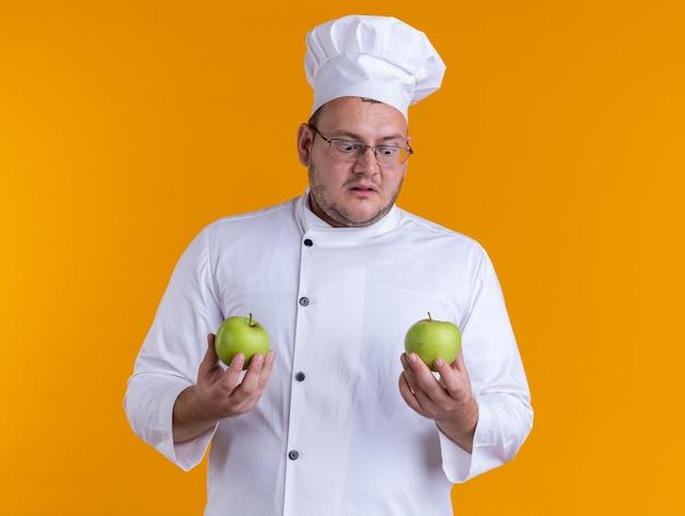 Überraschter erwachsener männlicher koch in kochuniform und brille mit äpfeln, die einen von ihnen einzeln auf orangefarbenem hintergrund betrachten