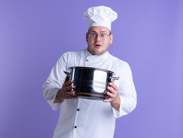 Überraschter erwachsener männlicher koch mit kochuniform und brille, der nach vorne schaut und den topf nach vorne streckt, isoliert auf lila wand?