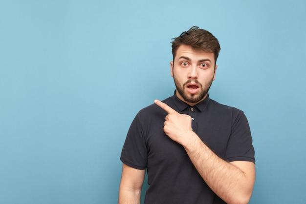 Überraschter erwachsener mann mit bart und dunklem hemd zeigt einen finger in richtung des leeren gesichts und schockierte blicke von der seite