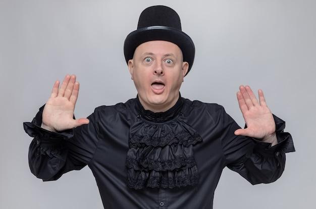 Überraschter erwachsener mann mit zylinder und im schwarzen gothic-hemd, der mit erhobenen händen steht