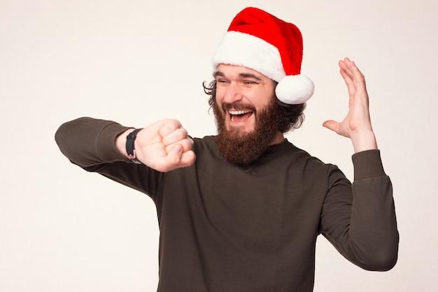 Überraschter erwachsener mann schaut zur weihnachtszeit auf seine neue armbanduhr.