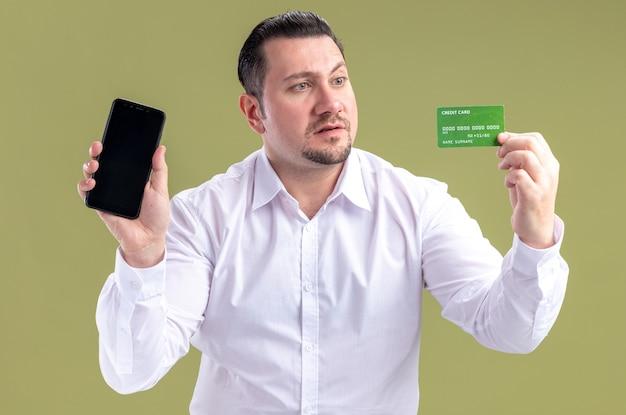 Überraschter erwachsener slawischer geschäftsmann, der telefon hält und kreditkarte betrachtet