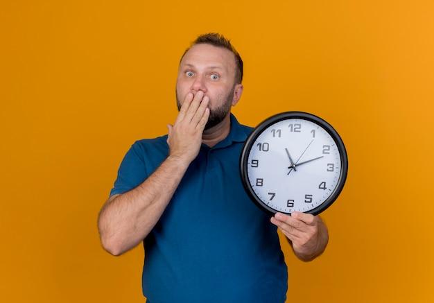 Überraschter erwachsener slawischer mann, der uhr hält hand auf mund schauend schaut