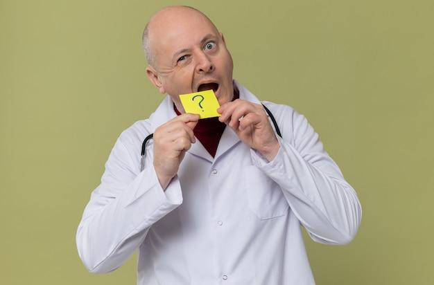 Überraschter erwachsener slawischer mann in arztuniform mit stethoskop, das fragenotiz hält