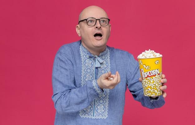 Überraschter erwachsener slawischer mann in blauem hemd mit optischer brille, der popcorn-eimer hält und auf die seite schaut