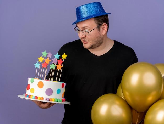 Überraschter erwachsener slawischer mann in optischer brille mit blauem partyhut betrachtet geburtstagskuchen, der mit heliumballons steht