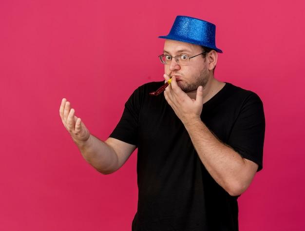 Überraschter erwachsener slawischer mann in optischer brille mit blauem partyhut, der die hand offen hält und die partypfeife bläst