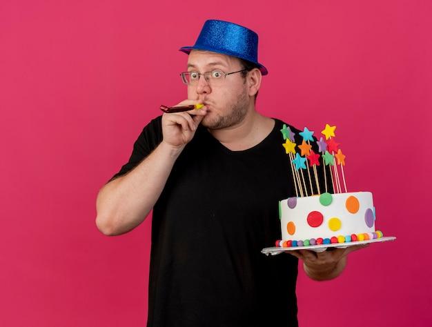 Überraschter erwachsener slawischer mann in optischer brille mit blauem partyhut hält geburtstagskuchen, der partypfeife bläst