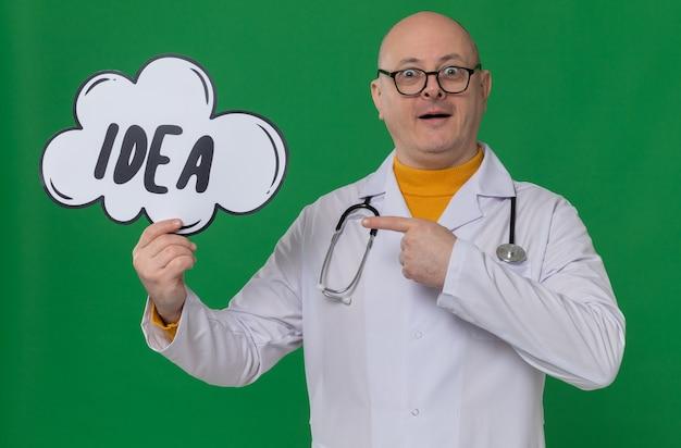 Überraschter erwachsener slawischer mann mit optischer brille in arztuniform mit stethoskop halten und auf ideenblase zeigend